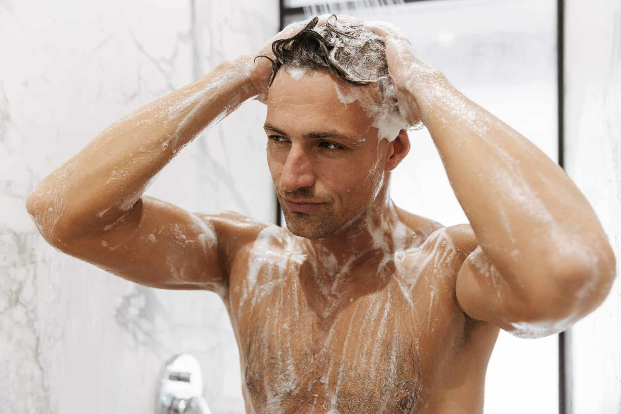 Man having a shower with a shower and washing hair