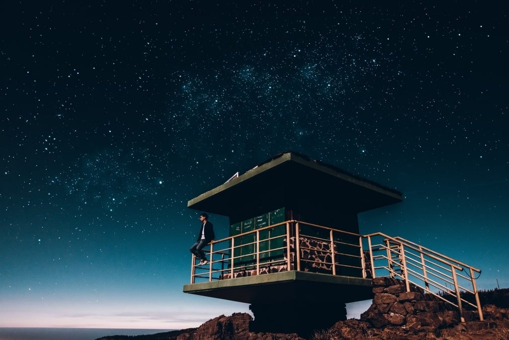 Man sits on beach looking at stars