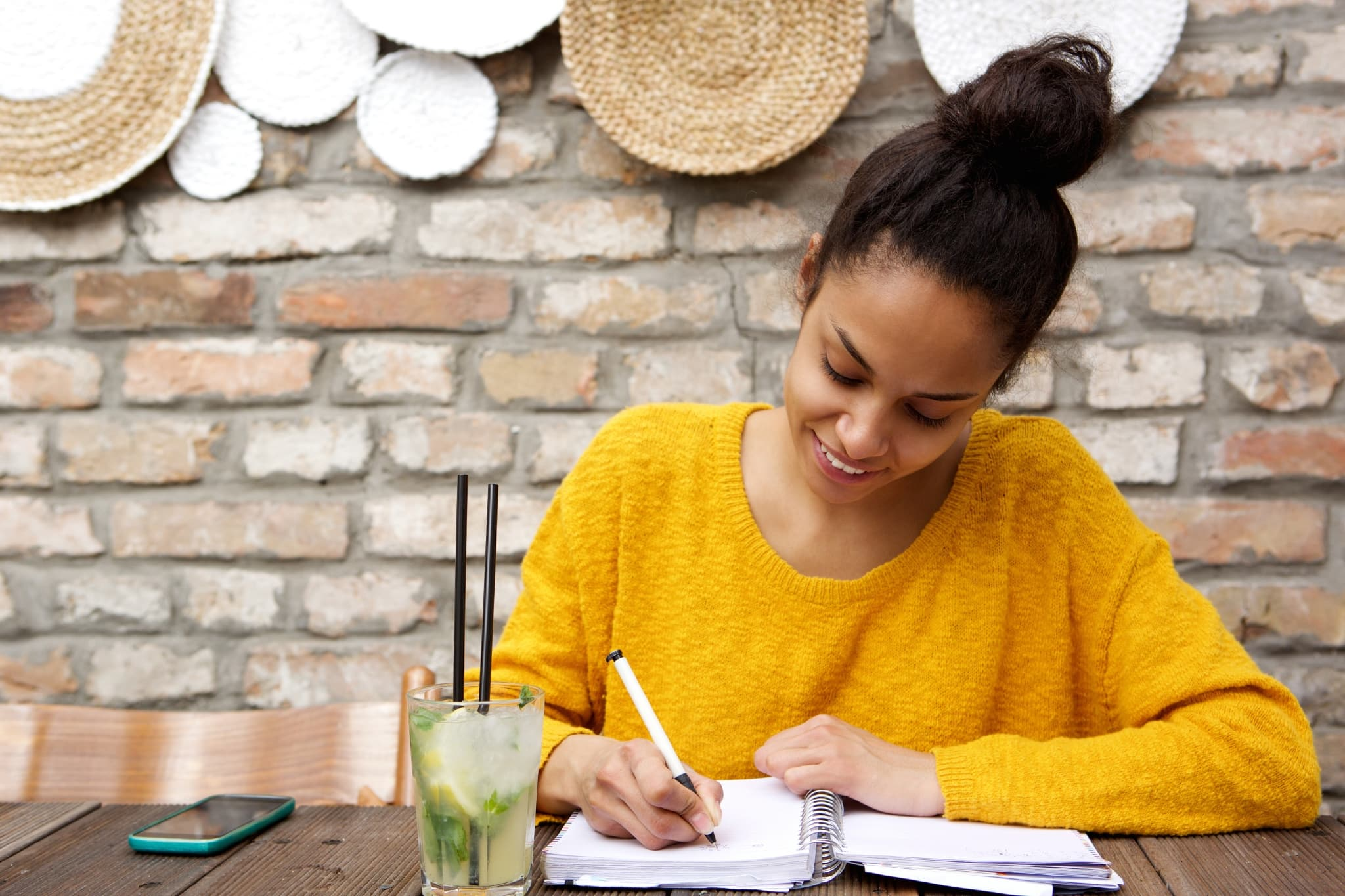IWD-beautiful-young-black-woman-writing-notes-at-cafe-PJ93C3Q-scaled.jpg