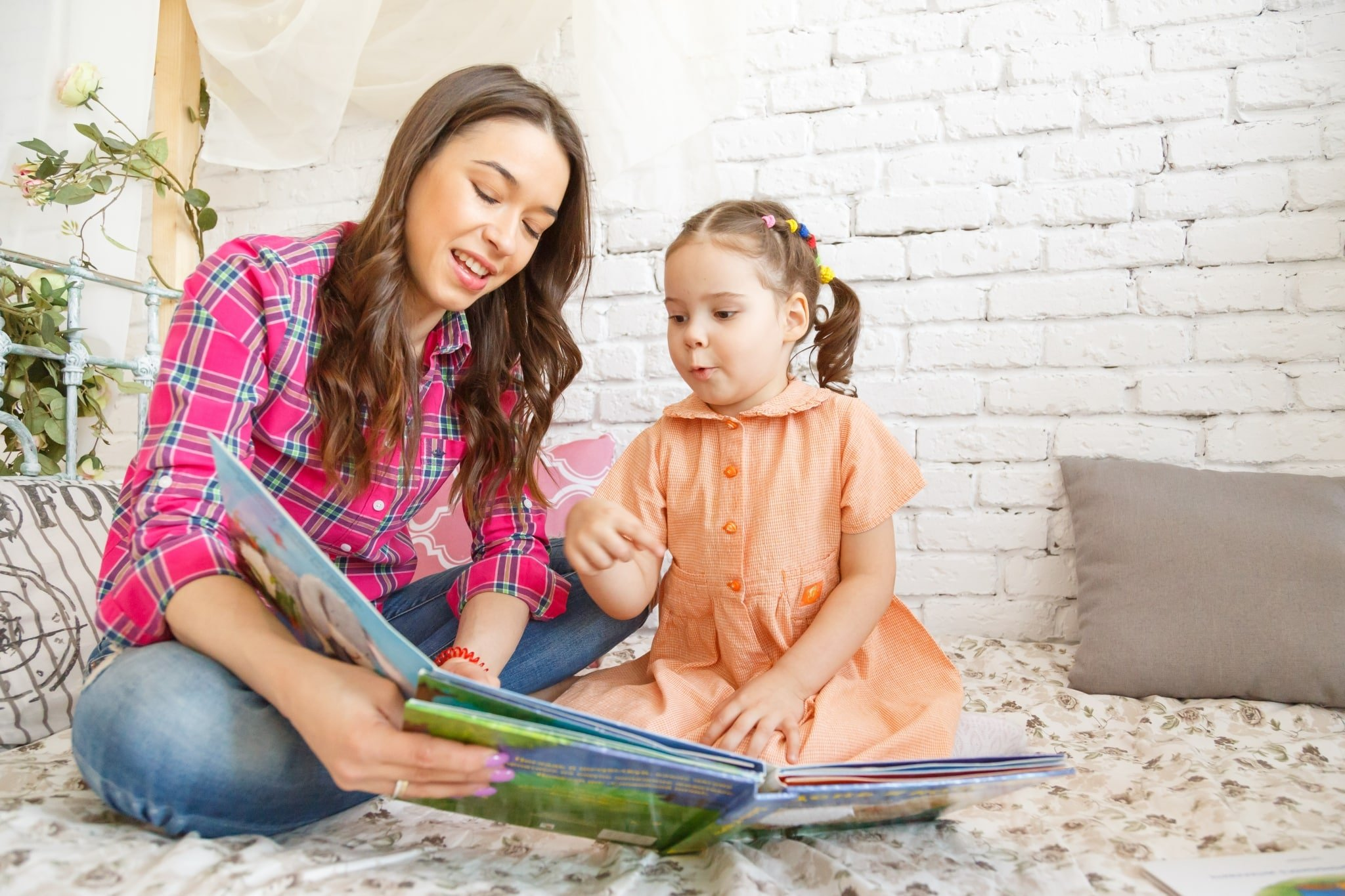 IWD2-young-mother-and-her-child-girl-reading-a-book-PFK6WNB-scaled.jpg